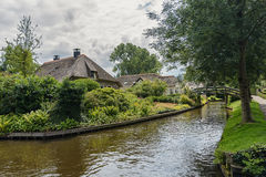 Farmhouse with a thatched roof and beautiful garden along a ditch Giethoorn, known as Dutch Venice Royalty Free Stock Photography