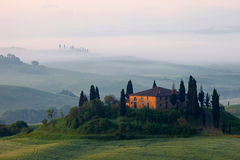 """Farmhouse in Tuscany in the morning mist. The solitaire standing farmhouse """"Casa Belvedere"""" is situated in the Orcia valley – a typical Tuscan landscape Stock Photos"""