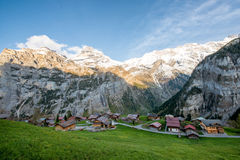 Farmhouse in village with swiss alps snow mountain in background. In Grindelwald, Switzerland. Country village in Switzerland Royalty Free Stock Photo