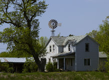 Farmhouse and Windmill. White Farmhouse and Windmill with Trees and Outbuildings Royalty Free Stock Photos