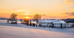 Farmhouse in a winter landscape at sunrise Royalty Free Stock Image