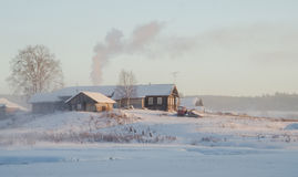 Farmhouse in winter. Rural house in the winter on the shore of a frozen lake. Arkhangelsk region, Russia Royalty Free Stock Image