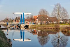 Drawbridge over canal near Smilde in Drenthe, The Netherlands. Farmhouses and drawbridge over canal near Smilde in Drenthe, The Netherlands stock image