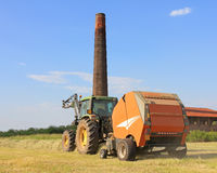 Farmig tractor in hay field. Tractor producing hay bales on cultivated field Royalty Free Stock Image