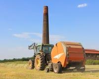 Farmig tractor in hay field Royalty Free Stock Image