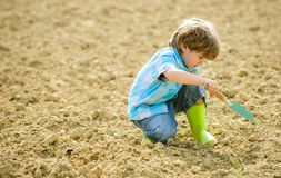 Farming and agriculture. small kid planting a flower. ecology life. Cultivation concept. earth day. new life. summer. Farm. happy child gardener. botanic worker royalty free stock images