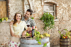 Farming couple drinking wine in their old farm. Farming couple drinking wine in their farm Royalty Free Stock Image
