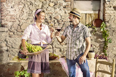 Farming couple making a toast with a glass of wine, harvest time Stock Photography