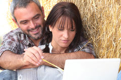 Farming couple. Sat with laptop computer Stock Image