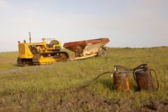 Farming Equipment. Old an rusted pieces of farming equipment and a yellow tractor in a  grassy field Stock Photo