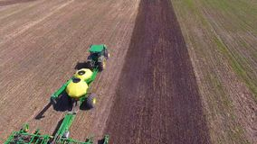 Farming equipment sowing seeds, top view. Special tractor plants crops on a big field stock footage