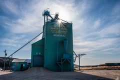 Grain elevator in prairies with sun peeking through Royalty Free Stock Photo