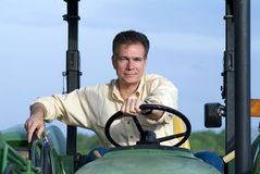 Farming Never Looked So Good. Handsome mature white male sitting comfortably on a big green tractor smiling contentedly and confidently Royalty Free Stock Photos