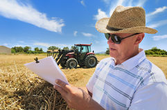 Farming Paperwork. A man with a confident expression uses a bale of hay to deal with paperwork  outdoors on a sunny day with blue skies. A tractor is seen in Royalty Free Stock Images