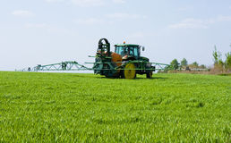 Farming tractor. Spraying a field Royalty Free Stock Image