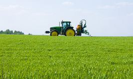 Farming tractor. Spraying a field Royalty Free Stock Photos