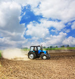 Farming tractor in a field. Farming blue tractor in a field, agricultural scene in summer Stock Photos