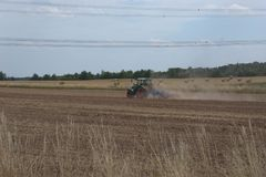 Farming tractor harrowing a dry field, after a summer harvest, and throwing up a lot of dust from the dry farmland. Hanging above the farmland, high tension Royalty Free Stock Image