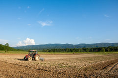 Farming with tractor and plow in field with mountain Papuk in th Royalty Free Stock Photo