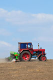Farming tractor plowing. Under blue sky Royalty Free Stock Photos