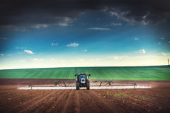 Farming tractor plowing and spraying on field Stock Images