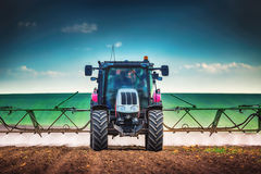 Farming tractor plowing and spraying on field Stock Image