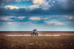 Farming tractor plowing and spraying on field Stock Photos