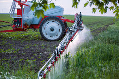 Farming tractor plowing and spraying on field Stock Photography