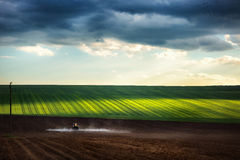 Farming tractor plowing and spraying on field Royalty Free Stock Photo