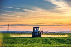 Farming tractor plowing and spraying on field, sunset. Farming tractor plowing and spraying on field at sunset Royalty Free Stock Photos