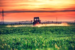 Farming tractor plowing and spraying on field by the sunset. Farming tractor plowing and spraying on field at sunset Royalty Free Stock Photography