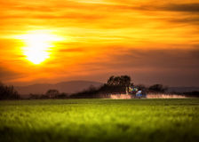 Farming tractor plowing and spraying at sunset royalty free stock photo