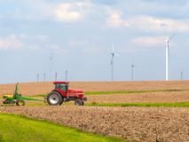 Farmer on tractor seeding by wind farm Royalty Free Stock Photography