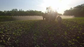 Farming tractor spraying on field with sprayer, herbicides and pesticides at sunset. Farm machinery spraying insecticide