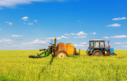Farming tractor spraying green field Royalty Free Stock Photo