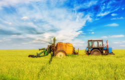 Farming tractor spraying green field Stock Photography