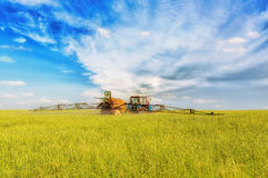 Farming tractor spraying green field. Beneath blue sky with white clouds Stock Photo