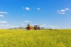 Farming tractor spraying green field Stock Photos