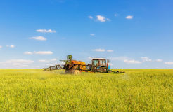 Farming tractor spraying green field Royalty Free Stock Photos