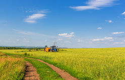 Farming tractor spraying green field Stock Images