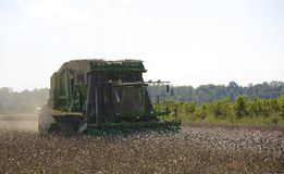 A Farming Tractors Gather Cotton. A piece of heavy machinery harvest cotton from a field royalty free stock photos