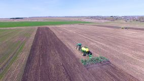Two tractors work on one field, top view. Farming tractors sow crops on one field stock footage