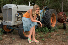 Farming vacation.3. Teenager sitting on a tractor's front wheel Stock Image