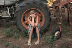 Farming vacation. Young girl sitting on a tractor's wheel Stock Photography