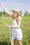 Farming Woman With Rope. Working On A Green Pastoral Landscape A Farming Woman Swings A Rope Above Her Head To Catch A Stray Farm Animal Royalty Free Stock Photography
