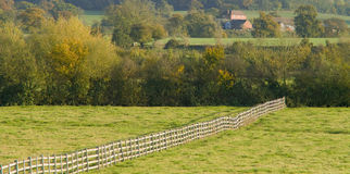 Farmland. Empty field with fence farmhouse in distance Royalty Free Stock Images