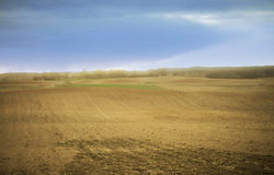 Farmland in early spring with a field ready to be sown. Farmland soil cultivated and ready to be sown Stock Photography