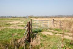 Farmland gate. Country walk along rural Norfolk Broads farm land. Path UK. Wood and metal gate in the countryside. Access rights for walkers. Scenic landscape stock images