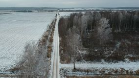 Farmland gravel road in winter and frosty forest, aerial view stock video footage