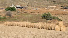 Farmland with hay bales after harvesting Royalty Free Stock Photos